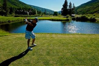 Greg Castillo, of Los Angeles, winds up and tees off at the recently opened 18th hole at the Vail Golf Club on Tuesday. After months of construction and controversy, the 18th now boasts a 190-yard carry—from its farthest of five tees—over two bodies of water.
