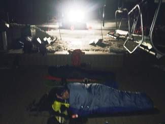 Nate Dogggg sleeps under the lift as groomers prepare the mountain for opening day Friday at Arapahoe Basin in Summit County.