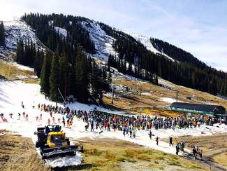 A crowd of skiers waits at the bottom of the Black Mountain Express lift during Arapahoe Basin's opening day Friday.