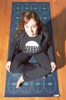In this March 7 photo, Elizabeth Morrow poses on her specially designed Yoga by Numbers mat in Bow, N.H. The mat gives true yoga beginners a step-by-step roadmap to learn poses at their own pace.