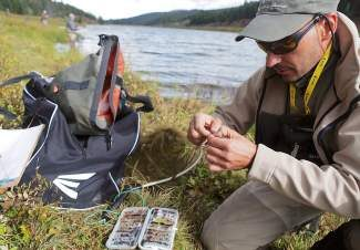 Team Naranja's Yann Caleri from France, right, ties a different fly to his line during day 3 of the America Cup fly fishing tournament at the Black Lake on Vail Pass.  The recent rain, which washed out much of the Colorado River, meant decision to move one of the competition locations from the Colorado River to Black Lake.