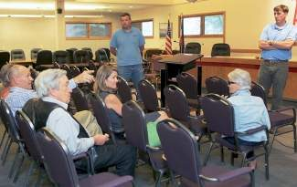 Part-time resident, Ron Martell, left, Avon Town Councilmen, Todd Goulding, left, and Chris Evans, center standing, questions about the new Wyndham timeshare building currently under  construction in Avon, during a public meeting about it Wednesday at the Avon town Council building in Avon. Both councilmen also work for Evans-Chaffee construction, who has the building construct for the new building.