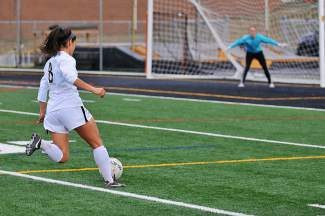 Palisade's goal keeper Katie Dunn prepares herself as Battle Mountain's Acacia Ortiz charges the goal in Edwards on Thursday. Ortiz had the finishing blow in a 4-0 victory over the Bulldogs.