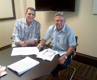 Michael and John Slevin, of Colorado Properties, sign the contract to join Berkshire Hathaway HomeServices.