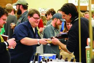 Boulder resident Eric Baumann, with Oskar Blues Brewing, left, holds his glass as Bell's Brewery's John Mallett pours him a sample during the Big Beers, Belgians & Barleywines Commercial Tasting at the Vail Cascade.