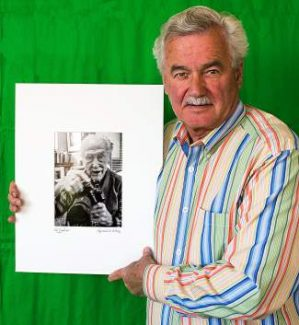 "Raymond Bleesz holds a portrait he took entitled, ""Hal Gould, Master Photographer, Curator."""