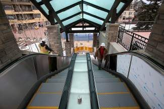 Chris Hill, Right, of Summit Sealants, walks up one of two new escalators being installed near the Beaver Creek ice skating rink as part of several improvements nearing completion Saturday around Beaver Creek Village.  Construction is slated for completion in time for opening week of the ski resort.
