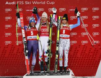 Lindsey Vonn, center, of the United States, celebrates her first place finish on the podium with teammate and second-place finisher Stacey Cook, left, and third-place finisher and teammate Julia Mancuso following the women's World Cup downhill ski race in Lake Louise, Alberta, Saturday, Dec. 6, 2014. (AP Photo/The Canadian Press, Jeff McIntosh)
