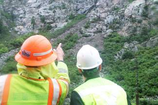 CDOT workers study the hillside from which rocks fell Thursday morning onto Interstate 70 in Glenwood Canyon.