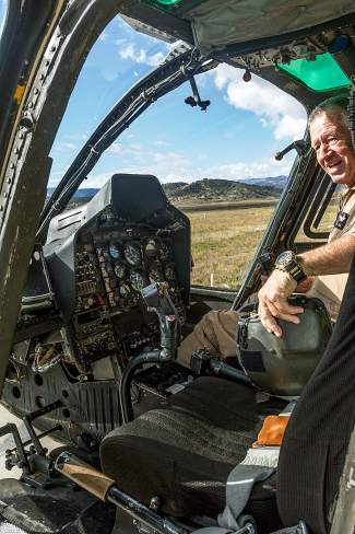 Longtime HAATS helicopter pilot Carl Gray sits in the cockpit of his Bell OH-58 Kiowa helicopter preparing for their final flight Wednesday in Gypsum.