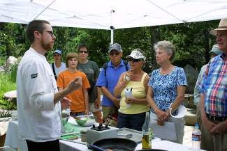 A local chef chats with attendees at a previous Chefs in the Garden cooking demonstration.