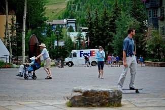A young man goes one way on a skateboard as an elderly couple goes another through Vail on Tuesday. Town of Vail officials are trying to pinpoint the market for the next generation of Vail tourism.