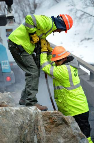 A pair of Colorado Department of Transportation road crew members use a jack hammer to drill into a boulder on Interstate 70 in Glenwood Canyon following an initial rockfall event the morning of Feb. 15. A bigger rockslide later that day ended up closing I-70 through the canyon for six days.