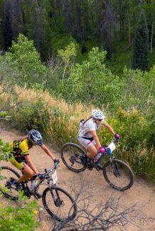 Rita Gutierrez, right, and Jojo Pico catch their breath while riding on one of the only flat sections of the Davos Dash mountain-bike race on Wednesday in Vail.