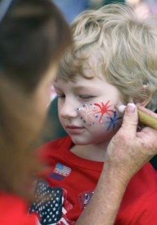 Elijah Chick-Jones, 5, right, shows off his patriotic spirit with a red, white and blue fireworks face painting by painter Rece Chilton, left, at the Stars, Stripes and Slides event in Beaver Creek in 2013.