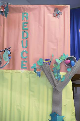 The backdrop from Avon Elementary's Earth Day play is seen adorned with recycled paper trees, used glue stick butterflies, and a message to reduce the usage of anything from water to driving a car.