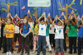 Avon Elementary students hold up plastic bottles while singing a song about recycling in Avon on Wednesday. The song was part of a play put on by the school for Earth day.