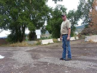 Ralph Seago stands in the middle of Violet Lane where the pile of yard waste overflowed and blocked him into his property on Sept. 8. In this photo, Seago's driveway is to the left and the entrance to the unmonitored public dumping ground is to the right. Seago said commercial companies are taking advantage of the dumping ground, which is only intended for residents, and the heavy traffic has been a problem for at least two years.