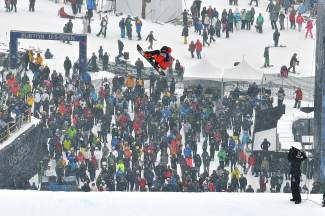 Crowds look on as Emil Ulsletten, of Norway, flies off the final jump during the Burton U.S. Open Snowboarding Championships slopestyle finals in Vail on Friday. Despite the heavy snowfall and low visibility, large crowds turned out to watch the event.