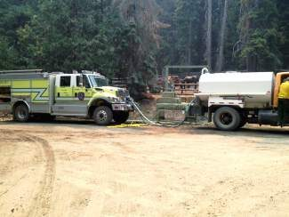 Equipment and crews from the Greater Eagle Fire Department and the Gypusm Fire Department prepare to battle wildfires in California.