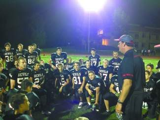 Eagle Valley football coach John Ramunno talks to a bunch of happy Devils after their 42-28 win against Cedaredge on Friday night in Gypsum.