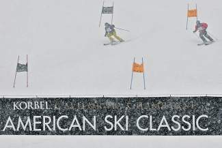 Heavy snow falls while Charlotte Adkins, left, goes head-to-head against Gary Stewart during the Korbel Ford Cup Team Races in the 2014 American Ski Classic on Vail Mountain on Saturday. Snow fell heavily for the majority of the races and was a large factor for many of the racers throughout the day.