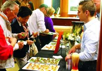 Peter and Brigitte Burger, left, of Lech, Austria, chat with Donovan Sornig right, and enjoy appetizers and punch prepared by Bol during last year's Gourmet on Gore Tasting Tour  at Betteridge Jewelers in Vail.