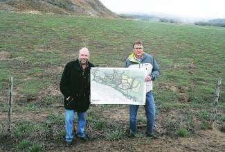 Haymeadow developer Ric Newman, left, and planner Rick Pylman poise with the project plan at the site of the proposal, east of the Eagle Pool and Ice Rink facility.