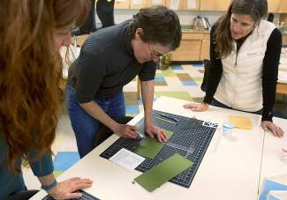 Paper artist Helen Hiebert, center, demonstrates to Berneil Bannon, left, and Amber Prince, right, how to cut the various layers of the paper shadow laterns to size during a Shadow Lantern workshop at Battle Mountain High School.