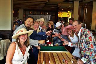 Sandra Lynch, Samten Aungae and Danielle and Kale Siess and a group of others try their hand at a horse-racing game at the Vail Derby Party.