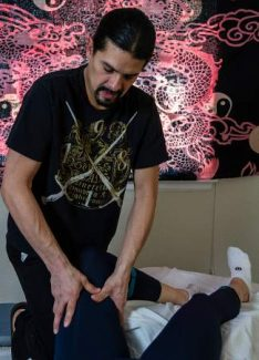 Hoshino therapist Mauricio Cadavid works the leg of a patient, finding the trigger points that react throughout the body.