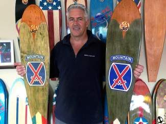 KOTA founder Mike Maloney displays his original 10th Mountain Division longboard, left, next to his new model. Behind him is a 2015 Alpine World Ski Championship board. Maloney says his boards have a camber shape that ski racers will appreciate.