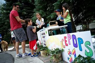 Taylor Cave, center, runs a lemonade stand with her brother James, second from right, and friend Adelle Dhanda, far right, in Vail on Monday. Cave is donating the profits to the Shaw Regional Cancer Center in Edwards, where her grandmother, who lives in Vail, was treated for breast cancer several years ago. Their profits will directly fund breast cancer research.