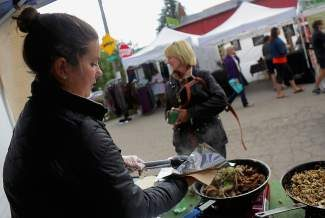 Nickys Quickie cook, Kim DeBettencourt, serves up a gyro to Ann Nestander from Chicago Saturday at the Minturn market in Minturn.  The Nickys Quickie Mediterreanian food stand is just one of a number of market vendors, who will benefit from the Vail Market extending their season into October.