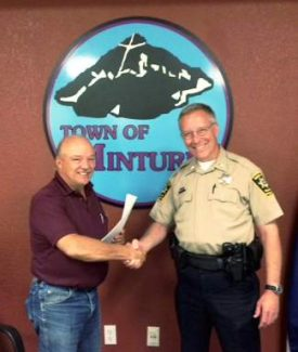 Minturn Mayor Hawkeye Flaherty, left, shakes hands with Undersheriff Mike McWilliam after Minturn completed an agreement with the Eagle County Sheriff's Office to provide police protection for the town. The move will save Minturn more than $100,000 a year.