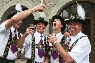 Members of the Denver Kickers Schuhplattlers tempt one of their younger members with beer as they enjoy beverages after their performance at the Lionshead Oktoberfest last weekend in Lionshead.