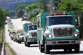 A long convoy  of wild land fire trucks makes its way up Highway 6 and 24 on their way to the commemoration of the 20th anniversary of the South Canyon Fire, held at Two Rivers Park Sunday.