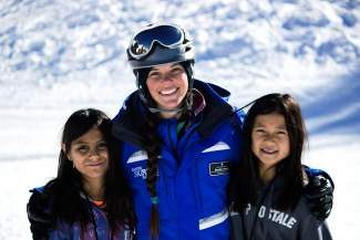 A Vail Resorts instructor enjoys a day on the slopes with two SOS Outreach participants.