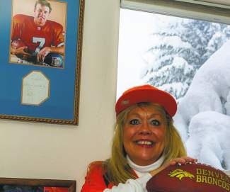 Superfan Debbie Thompson, of Edwards, shows off Denver Broncos memorabilia from her home on Friday, including a John Elway poster and signed note.