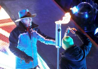 U.S. skiing legend Billy Kidd lights a torch during the opening ceremony for the FIS Alpine World Ski Championships, Monday, Feb. 2, 2015, in Vail, Colo. (AP Photo/Brennan Linsley)