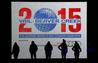 People stand in front of a screen during the opening ceremony for the FIS Alpine World Ski Championships Monday, Feb. 2, 2015, in Vail, Colo. (AP Photo/Brennan Linsley)