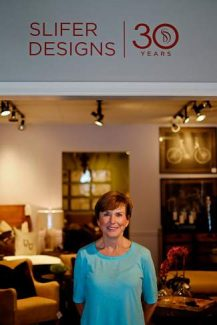 Slifer Designs founder Beth Slifer stands in her showroom in Edwards beneath a sign commemorating Slifer Designs' 30th anniversary. The iconic firm has been setting the standard for resort design since 1984.
