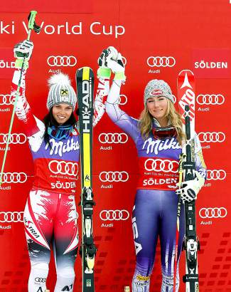 Austria's Anna Fenninger, left, and Mikaela Shiffrin celebrate on the podium after winning an alpine ski, women's World Cup giant slalom in Soelden, Austria, Saturday, Oct. 25, 2014. Fenninger and Shiffrin tied for the first place. (AP Photo/Giovanni Auletta)
