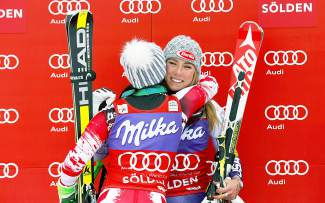 Mikaela Shiffrin, right, and Anna Fenninger celebrate on the podium after winning an alpine ski, women's World Cup giant slalom in Soelden, Austria, Saturday, Oct. 25, 2014. Mikaela Shiffrin and Anna Fenninger shared victory in the season-opening women's World Cup giant slalom on Saturday. The American teenager, who led after the first run, and the defending overall champion from Austria both finished in a two-run combined time of 2 minutes, 39.85 seconds. (AP Photo/Giovanni Auletta)