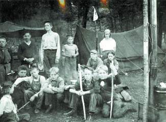 Boy Scouts camp in Tigiwon, ca. 1940s. One of the boys in the front row cut his foot on broken glass and a blanket that belonged to the girl sitting on the left side of the front row was used to wrap his foot until he could get medical attention.