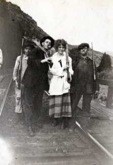 Jim Flynn, Claude Connors, Agnes Wheaty and Jay McDougall pose with rifles on the train tracks at Kent in 1918.
