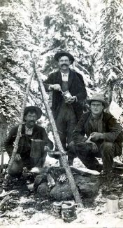 Clark Gates, left, Bert Gates, standing, and Walter Gates gather around the campfire during a 1920s era hunting trip.