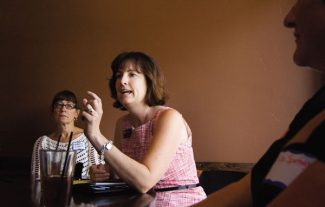 Theo Stroomer/Vail DailyKatherine Schmidt, of Eagle, left, and Liz Spetnagel of Eagle, right, listen to state representative Christine Scanlan during an Eagle County Democrats meeting at E-Town in Edwards on Thursday.