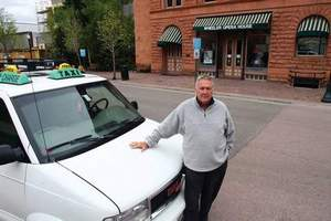 Aspen Times photoPhil Sullivan stands in front of his taxi in downtown Aspen. The city dropped charges against the cabbie after he obtained a business license on Tuesday.