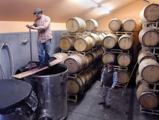 AP Photo/Cortez Journal, Sam GreenWine maker Joe Buckel stirs a vat of fermenting grapes while Jesus Castillo, right, looks on at the Sutcliffe vineyards in McElmo Canyon near Cortez, Colo. Winemakers in Montezuma County, which is in the extreme southwest corner of Colorado, report that the grape harvest was good this fall